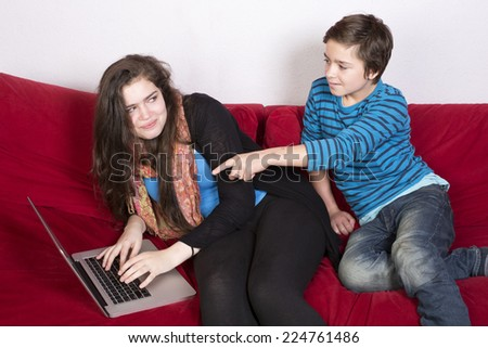 teenage girl and a boy looking at a laptop - stock photo