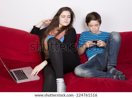 teenage girl and a boy looking at a laptop and phone - stock photo