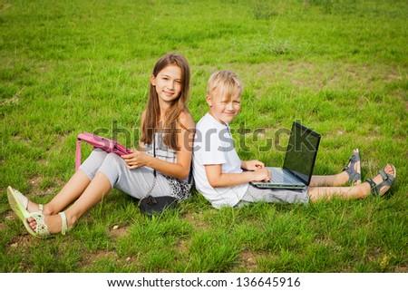 Teenage girl and boy doing homework on digital tablet. - stock photo
