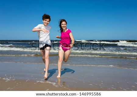 Teenage girl and boy jumping, running on beach