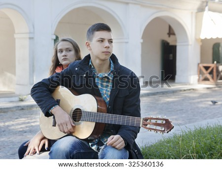 teenage girl and boy  with a guitar in conflict - stock photo