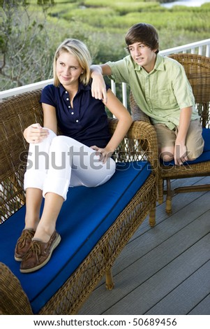 Teenage girl and brother sitting together on terrace - stock photo