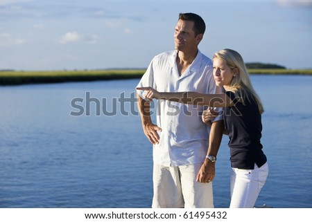 Teenage girl and father standing by water watching and pointing - stock photo