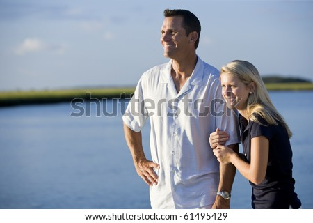 Teenage girl and father standing by water watching together - stock photo