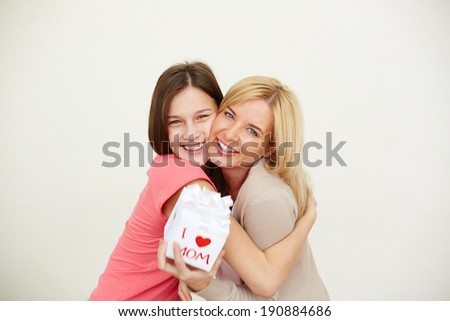 Teenage girl and her mom with small present looking at camera and laughing - stock photo