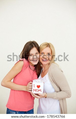 Teenage girl and her mom with small present looking at camera and smiling - stock photo