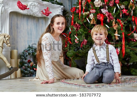 Teenage girl and little boy sit on floor under Christmas tree, boy sits among burning tealights which stand in shape of heart - stock photo