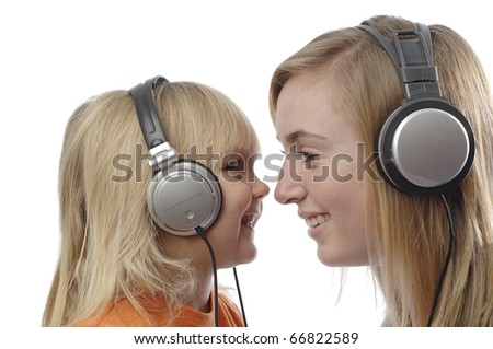 Teenage girl and toddler use headsets to listen music. - stock photo
