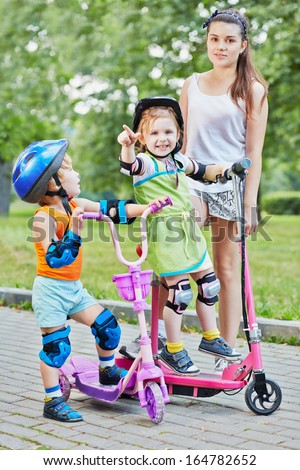 Teenage girl and two little children on scooters in summer park, focus on little girl