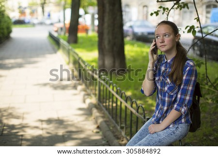 Teenage girl anxiously talking on the cell phone while sitting outdoors. - stock photo