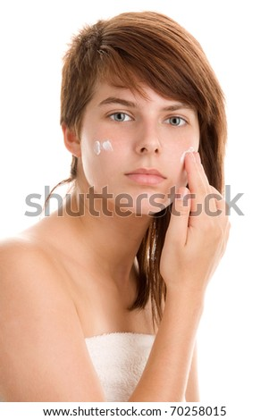 Teenage girl applying cream on her cheek