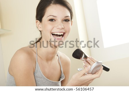 Teenage girl applying make up - stock photo