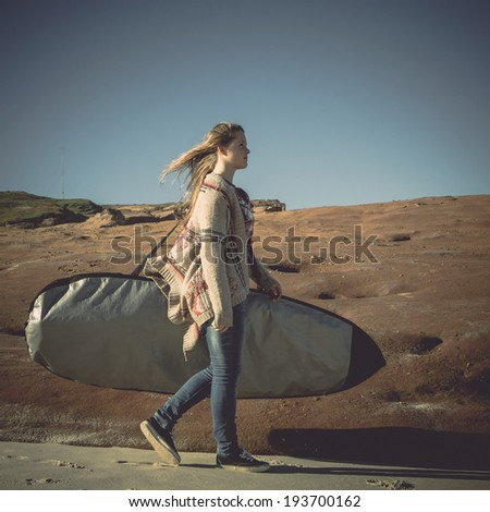 Teenage girl arrive to the beach with her surfboard