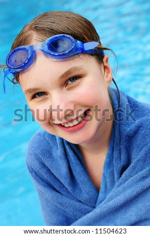 Teenage girl at the swimming pool wrapped in blue towel