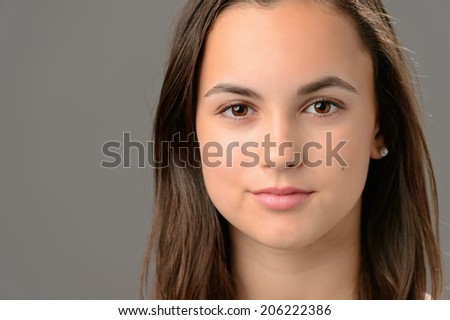 Teenage girl beauty face cosmetics brunette close-up on gray - stock photo