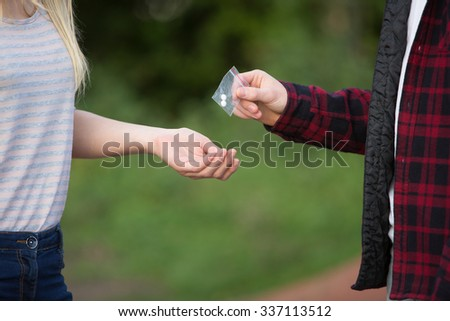 Teenage Girl Buying Drugs In Playground From Dealer - stock photo