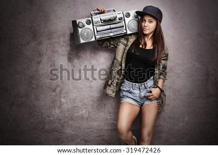 Teenage girl carrying a ghetto blaster over her shoulder and leaning against a rusty gray wall - stock photo
