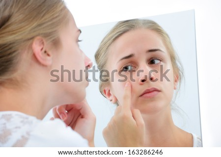 Teenage girl checking her face for pimple in the mirror - stock photo