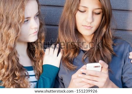 Teenage girl comforting her friend reading sad message - stock photo