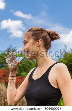 Teenage girl drinking a glass of water - stock photo