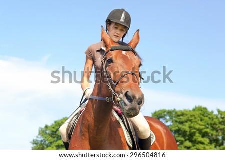 Teenage girl equestrian riding horseback. Vibrant summertime outdoors image. - stock photo