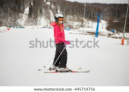 Teenage girl equipped for skiing on snowy slope at ski resort. - stock photo