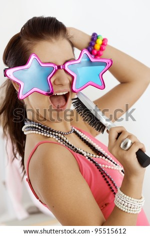 Teenage girl having fun at home, wearing funny glasses, singing to hairbrush.? - stock photo