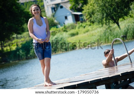 teenage girl having joyful time happy smiling & looking at camera on summer water outdoors background - stock photo