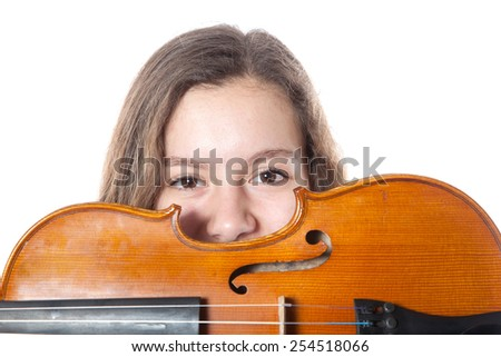 teenage girl hides behind violin in studio with white background - stock photo