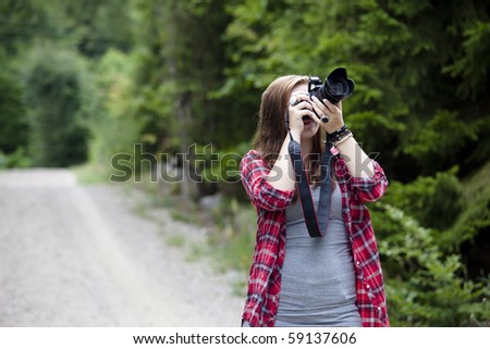 Teenage girl holding a camera shooting apicture outdoors - stock photo