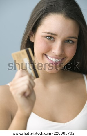 Teenage girl holding a credit card - stock photo