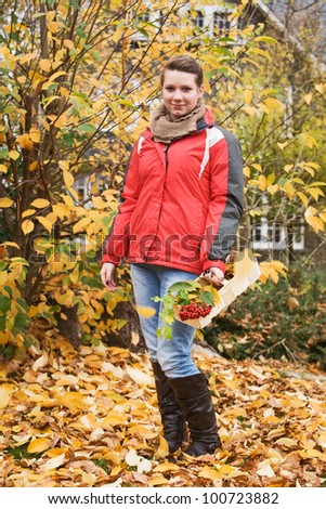 Teenage girl holding basket of autumn leaves and berries - stock photo