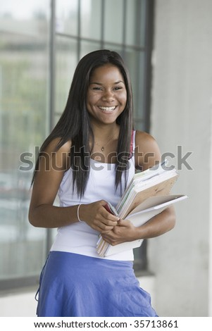 Teenage girl holding books and smiling in a school - stock photo