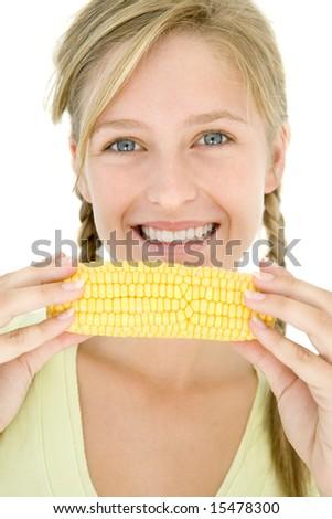 Teenage girl holding corn on cob and smiling - stock photo
