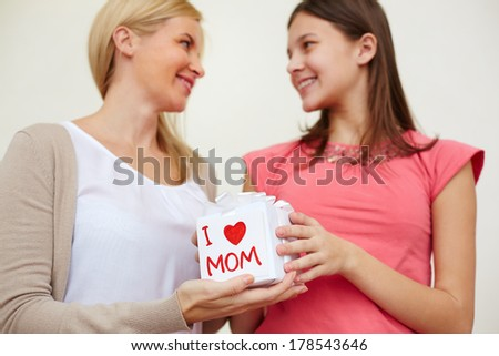 Teenage girl holding giftbox and giving it to her mom - stock photo