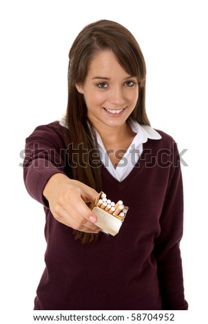 Teenage girl holding out packet of cigarettes isolated on white - stock photo
