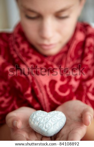 Teenage girl holding silver heart