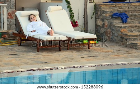 Teenage girl in a bathrobe by the pool - teenager resting after a swim in the oceanside pool on the Greek island of Crete - stock photo