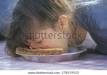 Teenage girl in a pie-eating contest, Knott's Berry Farm, CA - stock photo