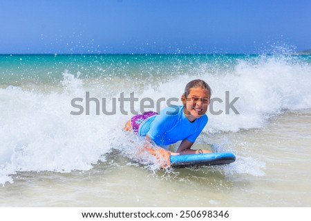 Teenage girl in blue has fun surfing - stock photo