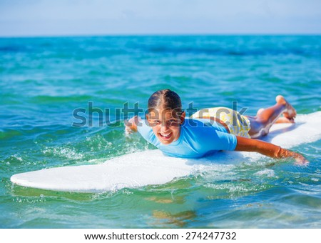 Teenage girl in blue learning to surf  - stock photo