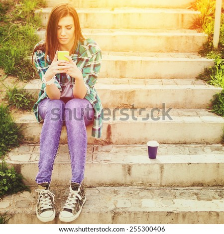 Teenage girl in casual clothes with smartphone and takeaway coffee texting sitting outdoors on stairs in park on sunny spring day. Retouched,vivid color filter,square format,instagram look,copy space  - stock photo