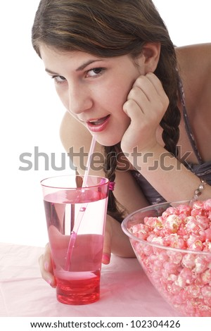 Teenage girl in halter top and long braids sips drink through a straw and looks up. Large bowl of pink popcorn and tall glass on table in foreground. Vertical, isolated on white with copy space.