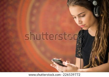 Teenage girl in headphones using her smartphone - stock photo
