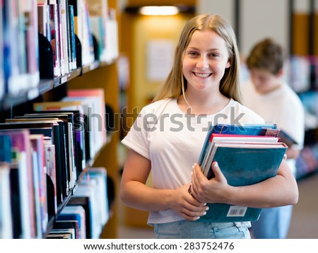 teenage girl in library choosing books - stock photo