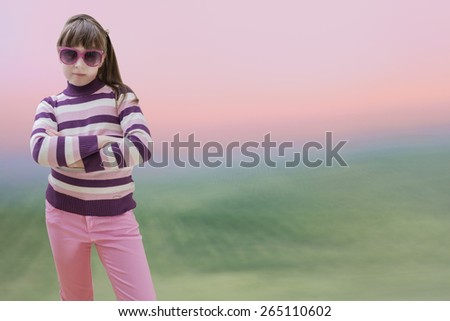 Teenage girl in pink wears sunglasses at sunrise background - stock photo