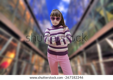 Teenage girl in pink wears sunglasses with modern shopping mall in background - stock photo