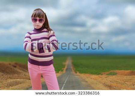 Teenage girl in pink wears sunglasses with road in background - stock photo