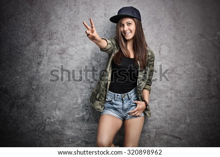 Teenage girl in trendy hip-hop clothes making a peace sign with her hand and posing in front of a rusty gray wall - stock photo