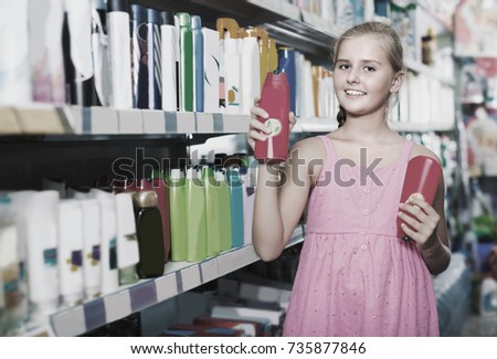 Teenage girl is choosing shampoo and conditioner for hair in the supermarket.